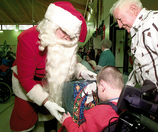 Robert Holder of Longview Ambucs is Santa Claus and gives a present to Shaun Patton nine years old as His Grandfather Herb Custer looks on Saturday afternoon at Truman S. Smith in Gladewater. By Darlene