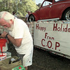 Ed Bowers with Citizens On Patrol (COP), pours paint for the group's Longview xams parade float Friday afternoon. Chris Matula photo.