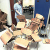 PT Interm. 4th grade teacher Gloria Bates will be sorry to see her old classroom chairs become extinct as she awaits the arrival of her new desks in her classroom at the new school Monday. Teachers spent the day competing with work crews getting the facility ready for its Jan. 6 opening. Matula photo.