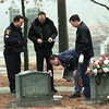 Investigating officers look at a possible piece of evidence near the victim.  Lester Phipps, Jr.