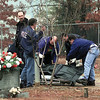 Longview Police officers load the victim onto a cart for transport to the morgue.  Lester Phipps, Jr.