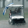Winona Williams holds a broken umbrella she found on the 9th hole as little protection against a driving rain that broke up the Alpine Golf Course Pro-Am Monday afternoon. Ray Hill drives the cart at breakneck speed to get to cover. Chris Matula photo.