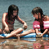8-year-old Christy Harper of Gladwater and sister Autumn, age 6, administer mud packs to each other while sitting on a sand bar at Gladwater Lake Wednesday afternoon.  Lester Phipps, Jr.
