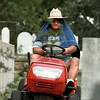 Charles Bright is well-protected from the heat and humidity as he mows the Marshall Hebrew Cemetery in temperatures in the upper 90s Wednesday. The cemetery is on the site of one of the first synagogues in Texas which has since moved to Longview and Bright has been taking care of the plots for ten years. Chris Matula photo.