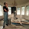 Cathy Williamson surveys the damage done to her dining room after flood waters rose ankle deep following tuesday's heavy rains. This is the sixth time her home has flooded on Clendenen Street in Greenbriar. Chris Matula photo.