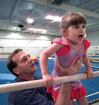 Mike Moore helps 3-year-old daughter Madison up onto the bar to work on her upper body strength.   Lester Phipps, Jr.