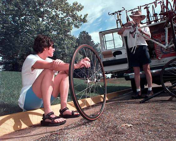 """Lisa Terry of Dallas waits for bicycle technician Alan Enslow to finish with a job so she can have a flat fixed.  """"I've been riding for three years and this is my first flat"""", said Terry.  Lester Phipps, Jr."""