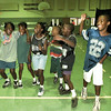"Kids at Camp Harvey celebrate winning a game where the line of six has to ""walk"" across the gym at Broughton Recreation Ctr by pretending their feet are tied to those of their neightbor. (l-r) Shatoya Davis (11), Whitney Horne (10), Kwinice Brookins (10), Sean Davis (9), Ontario Shaw (10) and Lasale Boyd (10). Chris Matula photo."