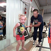 Stuart Tiner gives 2-1/2-year-old Sealie a hand as she begins to zip across the balance beam while sister Sadie waits her turn.  Sealie usually makes a fast pace along the beam and tries to pass up other children.   Lester Phipps, Jr.