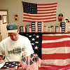 Sean Curry of Longview Canvas Products inspects a shipment of US flags Friday before putting them on display for Flag Day June 14. The large 10 x 15' nylon one in the background goes for $252. Chris Matula photo.