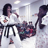Karate black belt Kathy Buroker demonstrates how to defend yourself from an attacker with 8-year-old Amber Ford.   Lester Phipps, Jr.