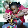 Girl Scout leader Sandra Waller helps 6-year-old Britnee Shadell with some crepe paper crafts under the pavillion at McWhorter park during one of the PARD summer programs.  Activities were moved under cover due to rains Tuesday morning.   Lester Phipps, Jr.