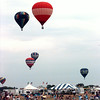 Balloons sail away from the first target area at the airport to their secondary target near the Neiman-Marcus Distribution Center at the Business Park.  Officials quickly cancelled the second target area due to increasingly high winds Sunday morning.  Lester Phipps, Jr.
