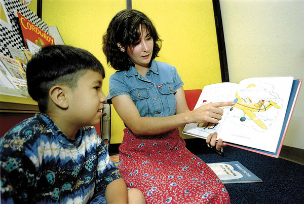Pine Tree bi-lingual teacher Marta Garcia reads a book with Kindergartener Geovany Romero during a summer session.  Lester Phipps, Jr.