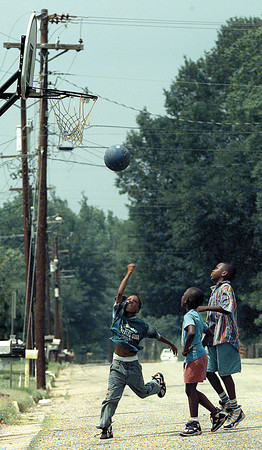 ANDRE WILLIAMS, 10, ATTACKS THE HOOP AS HIS OPPONENTS KAYLDON KELLY, LEFT (7), AND XAVIER FIELDS, 11, CAN ONLY WATCH DURING A LITTLE STREET GAME AT THE INTERSECTION OF FULLER AND DUDLEY STREETS. CHRIS MATULA PHOTO.