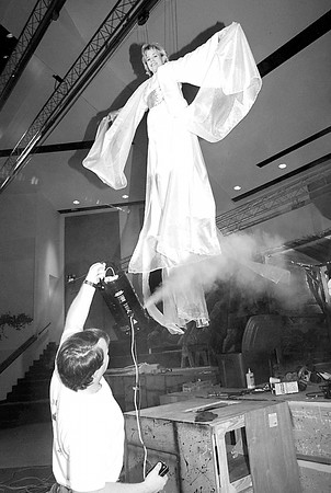 Carol Rye of Longview portrays an Angel as Clay Perkins of Longview trys to see how the fog machine works with the angels in the air Saturday afternoon at Mobberly Baptist in Longview. By Kevin Green