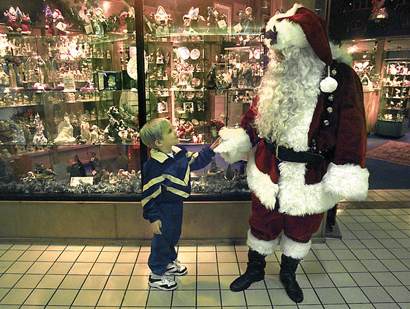 Marshall Pryor, 4, of Houston gets a one-on-one session with Santa as the jolly elf takes a quick break from hearing Christmas wishes Friday at Longview Mall. The day after Thanksgiving is traditionally the busiest shopping day of the year. Chris Matula photo.