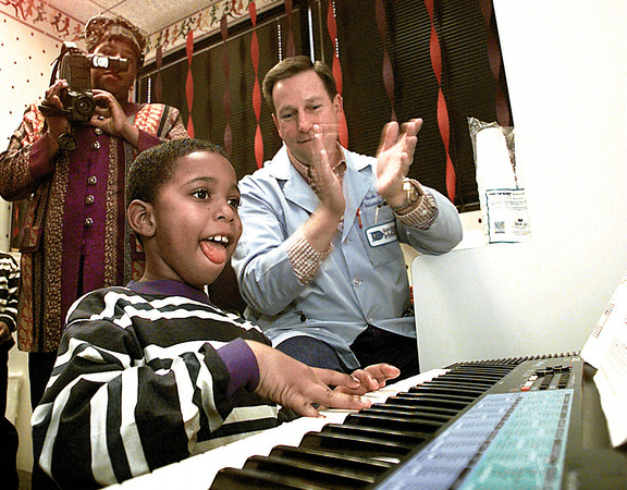 "Cancer survivor Montreal Sparks receives accolades from friend and Pediatrician E. A. Clark as he plays ""Amazing Grace"" on the keyboard at his birthday party at the Diagnostic Clinic in Longview.  Spark's mother, Teresa, captures the entire event on video.  Lester Phipps, Jr."
