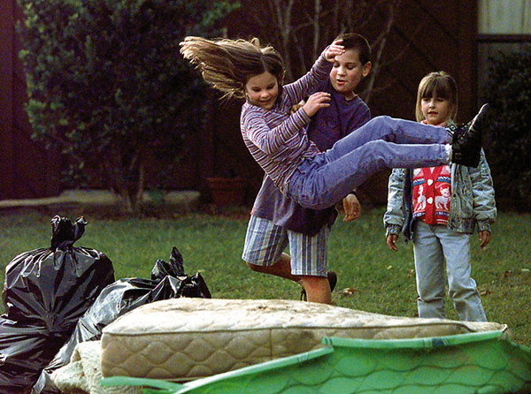 Amy Grimsley, 8, watches her landing pad as her friend Ryan Pratt, 10, launches her onto a discarded mattress in the 100 block of Creekside while Heather Pace, 6, waits her turn. Chris Matula photo.