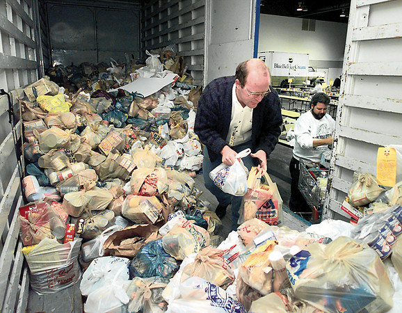 Lee Stanton, foreground, and Stan Dulaney, both the Texas Dept. of Human Services, sort food brought in by the Boy Scout collection drive last weekend at the Maude Cobb Center  Tuesday. Chris Matula photo.