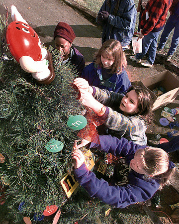 Hughes Springs Junior High students Tasha Neal, Lindsay Niblett, Melinda Peace and Stephanie Bishop deck their tree with M&M's memorabilia at the Hughes Springs City Park.  Lester Phipps, Jr.