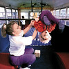 """Gymnastics instructor Jodi Parrish helps 4-year-old Lindsey Conway perform a back-flip aboard Piney Wood Gymnastic's """"Tumblebus"""".  Lester Phipps, Jr."""