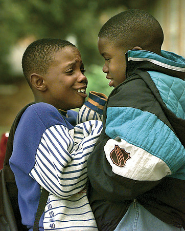 Marquaus Simmons, 8, can't get wartm as he huddles with friend Tamarcus Parmer, 9, for warmth in front of Pittsburg Primary School Tuesday afternoon following a cold snap early Tuesday morning. Chris Matula photo.
