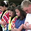 PT High School students Emily Martin, Julie Farrell, Amanda Whiddon and Kris Duplissey bow their heads in prayer with a group of students who gathered around the flag pole in front of the school Wednesday morning for prayer.  Lester Phipps, Jr.