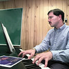 St. Mary School band director Tod Sechrist tickles the ivories during a break between classes.  Lester Phipps, Jr.