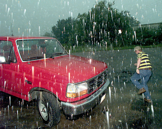 Peter Gerbine III runs to his truck in a driving rain after abandoning hopes of trying to put up a new sign at Mr. C's drive-in on Marshall Thursday afternoon. Chris Matula photo.