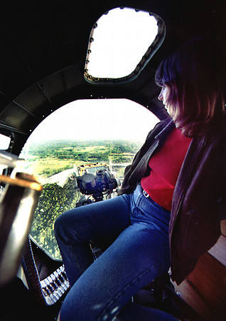 Donna Kuperman the manager of Sunpoint Aviation looks out through the bombadiers window in the nose of the B-17 during a media flight Sunday afternoon at the Gregg County Airport. Kevin Green
