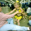 Sandi Hitt dances with her daughter Courtney, 3, as the little girl prepares to go onstage with the rest of Michelle's Main Event twirlers Thursday for the cheerleading competition at the Northeast Texas Regional Fair. Matula photo.
