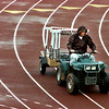 White Oak track coach Richard Burks hauls hurdles onto a very wet track fro the District 16-3A meet Friday afternoon. Matula photo.