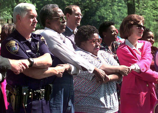 Left to right  Longview Police officer Jesse Garner the beat 50 P.A.R.  officer left, Hosea Hutchins, Gloria Burns and Nancy Lucenay all join hands as they sing the closing song (Reach Out and Touch Someone) during the ground-breaking ceremony for the city's resource center Monday morning near Stamper Park in Longview. Kevin Green