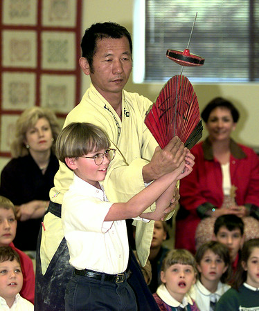 Stewart Linthicum a second grader at Trinity School of Texas gets some instruction on stick balancing  by Masaji a performer from Epcot tuesday morning at Crisman Preparatory School in Longview. Kevin Green