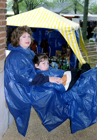 Rhonda Pitts and her daughter (you must get ID from Bill-CM) wait out a rainstorm in Hughes Springs as the Wildflower Trails was essentially washed out Saturday. Bill Thompson photo.