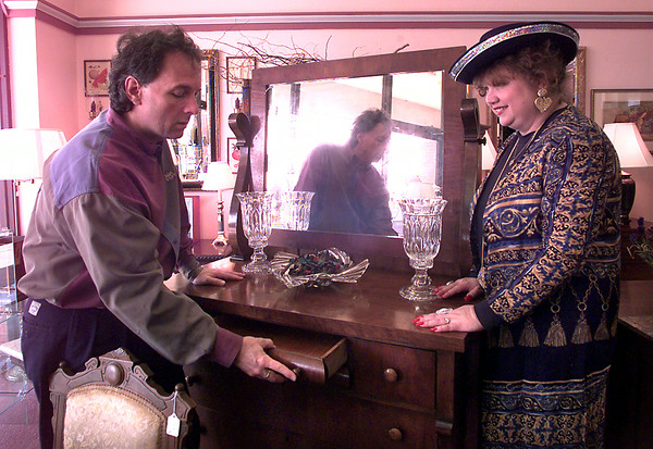 Greg and Sheila Rainer of Rainer's Unique Gifts of Longview look over a circausian, walnut burl, Empire period late 1800's dresser at their shop. Kevin Green