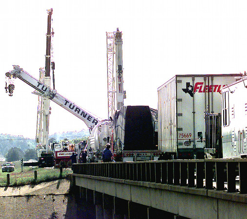 Workers with Turner Bros. Crane & Rigging work to get a crane upright that fell over I-20 west of Estes Parkway Tuesday afternoon. Kevin Green