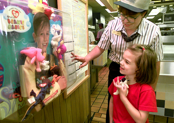 Tracy Newlin manager of the McDonlald's on Estes Parkway shows Morgan the 5 year old daughter of Harold and Cindy Greer of Bethany, Okla. the display of beanie babies Thursday morning in Longview. The beanie babies are the latest happy meal toy. Kevin Green