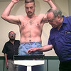 Michael Baggett, of Longview, raises his arms as he weighs in for tomorrow night's match, while Dickey Cole, right, the State of Texas Boxing Comissioner oversees the weigh-in. Kevin Green