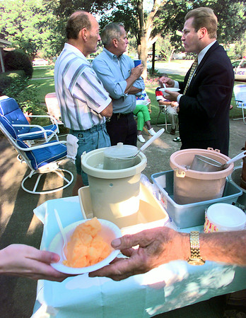 U.S. Congressman Max Sandlin, right, partakes in the homemande ice cream and fellowship with Loongview Police Chief Leroy Hamilton, middle, and Bill Bickham in the 100 block of W. Edgfefield during the National Neighborhood Night Out Tuesday. Matula photo.