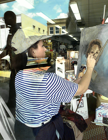 Sherry Shelton, of Longview, paints a portrait in the window of Berry's Custom Framing and Gallery, in downtwon Longview Thursday afternoon. Artists from the Upper Level Artists Gallery will be taking turns as they paint every Thursday until Christmas in the window from 11am to 2pm in the afternoon. Kevin Green