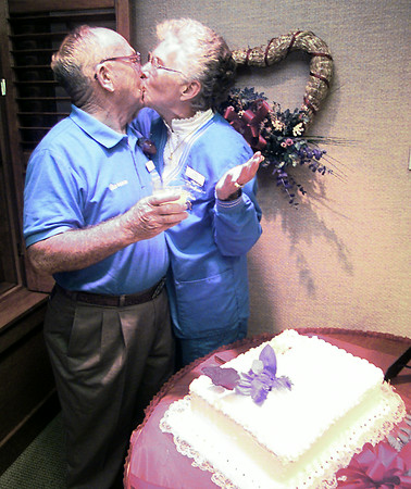 Clarence and Jean Norton, previously Adams, kiss over their wedding cake after tying the knot Friday evening at the Longview Cancer Ctr. where both volunteer. Both of their spouses passed away from cancer and the two met using the center's services. Matula photo.
