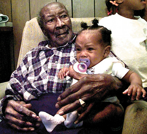 Robert Mitchell celebrates his 110th  birthday with family Sunday afternoon as he holds his great-great-great granddaughter Rayven Henry, 4 months at his home out side of Pittsburg. Kevin Green