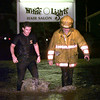 Longview firemen Aaron Deary left, and Mike Small come out of the swollen creek on Baylor at near McCann road after rescuing a man from his car stuck in the water Thursday night in Longview. Kevin Green
