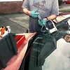 Jimmy Laws with On The Spot Window Repair uses a resin that reacts with ultraviolet light to bond cracks and road dings on a windshield in front of Martin Insurance on Methvin Thursday evening. Laws will come to the customer to fix their glass. Matula photo