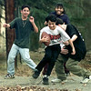 David Solis, 11, is dragged out-of-bounds by Kevin Evans, 13 in black, as they play street football with Daniel Solis, 13 left, and Leslie Warren, 13 background, on Ridgelea in Longview Friday. Matula photo.