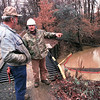 East Texas Oilfield Services vacuum truck operator Bob Kinney and cleanup tech Tom Fogel discuss a plan of action on where to begin the removal of the petroleum in ________ creek Wednesday morning.  Lester Phipps, Jr.