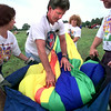 Debbie Conway, left, and her husband Tom Conway, far right, both of Longview hold the bag open as pilot Dennis Barrett packs the balloon and his wife Lea in background get ready for the next flight after Friday morning flight was cancelled due to weather. Kevin Green
