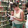 Kyle McMurrey-9, left, looks around his sisters arm as she Katy-13, a student at Trinity School of Texas, goes over her list of school supplies, while her mom Mary Jo McMurrey looks on, at the Sav-on store on Judson Rd. Thursday afternoon in Longview. Kevin Green